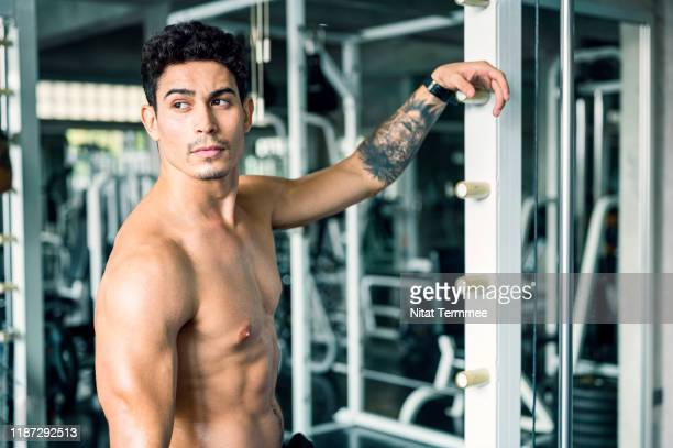 healthy lifestyle, exercising and people concepts. tattoo muscular men with perfect abs excercise on a barbell, resting after weightlifting workout at gym. - handsome bodybuilders stock pictures, royalty-free photos & images