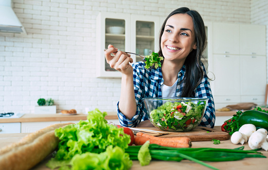 Healthy lifestyle. Good life. Organic food. Vegetables. Close up portrait of happy cute beautiful young woman while she try tasty vegan salad in the kitchen at home. 1151268627