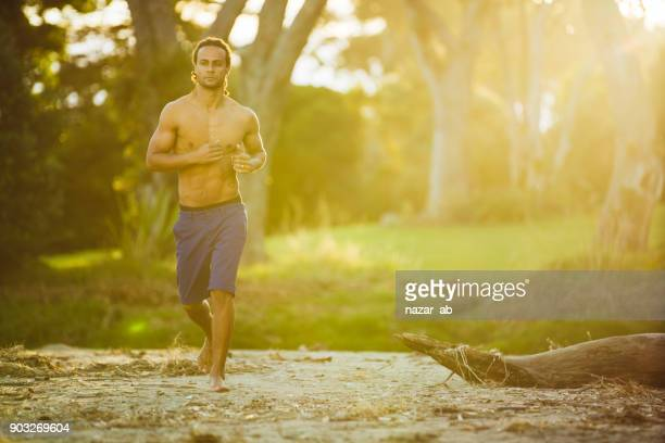 Healthy lifestyle young mixed race man running out in bush.