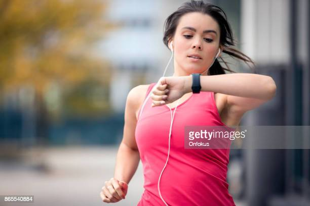 healthy lifestyle young woman running and looking at smart watch - wearable computer stock pictures, royalty-free photos & images