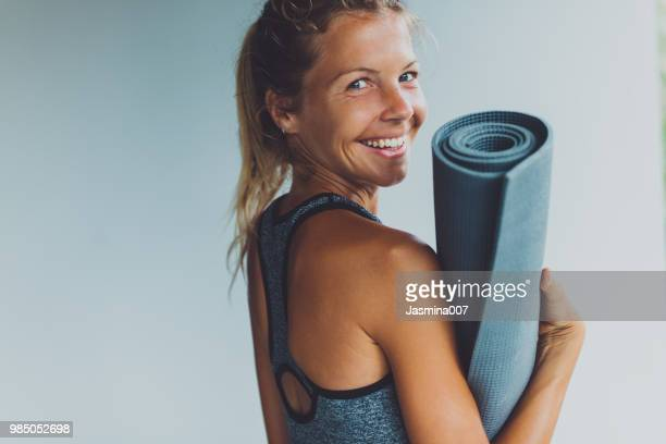healthy living- young woman with yoga mat - pilates foto e immagini stock
