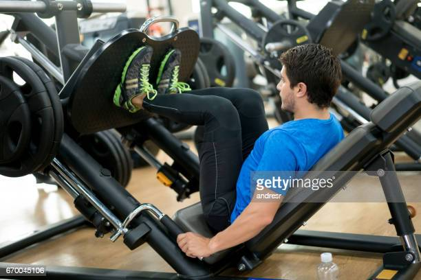 Healthy man exercising at the gym on a leg press machine