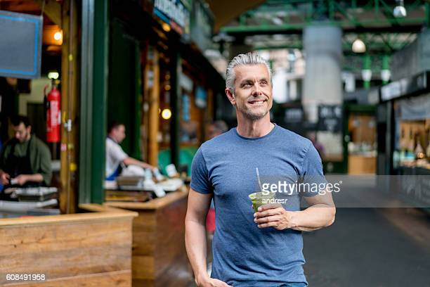 healthy man having a smoothie - 50 54 years stock pictures, royalty-free photos & images