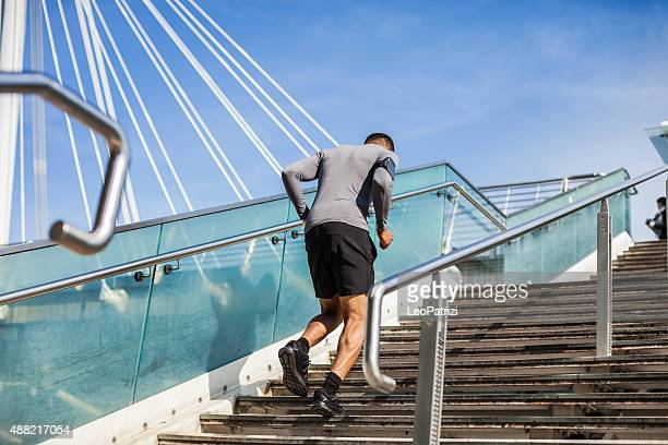 Healthy man running up and down on steps
