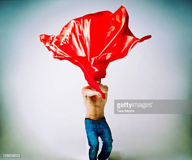 healthy man throwing red cape in air