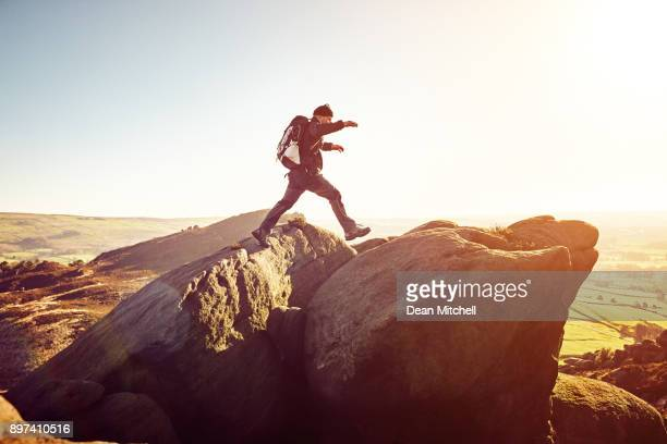 Healthy mature man with backpack jumps over rocks
