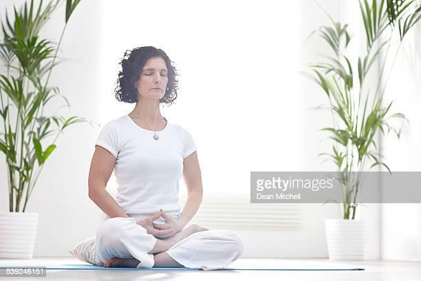 Healthy mature woman meditating