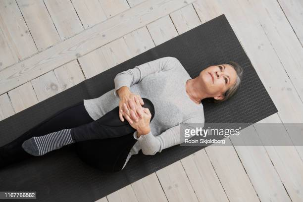 healthy mature woman stretching on yoga mat - oresund region stock pictures, royalty-free photos & images