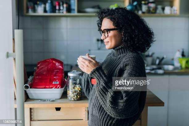 gesunde morgengewohnheiten: eine junge mixed race frau, die heißen tee in der küche trinkt - ceremony stock-fotos und bilder