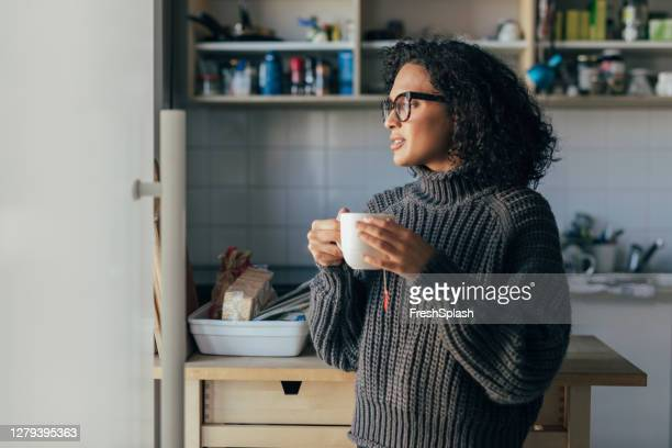 healthy morning habits: a young woman drinking hot tea in the kitchen - drinking stock pictures, royalty-free photos & images