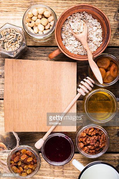 Healthy morning muesli ingredients and wooden plank with copy space . Raw rolled oats, dried fruits, seeds, honey, nuts and milk on rustic wooden board, top view