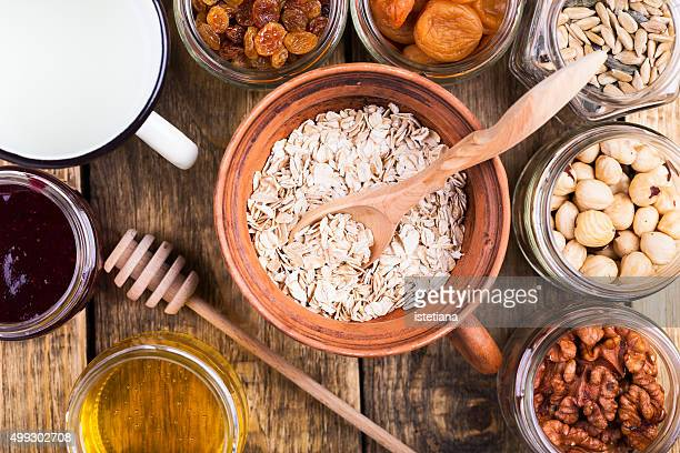 Healthy morning muesli ingredients. Raw rolled oats, dried fruits, seeds, honey, nuts and milk on rustic wooden board, top view