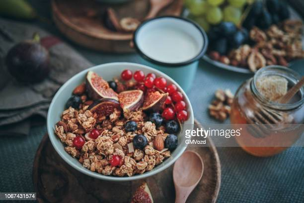 healthy muesli with fresh figs, blueberries and redcurrants for breakfast - granola stock pictures, royalty-free photos & images