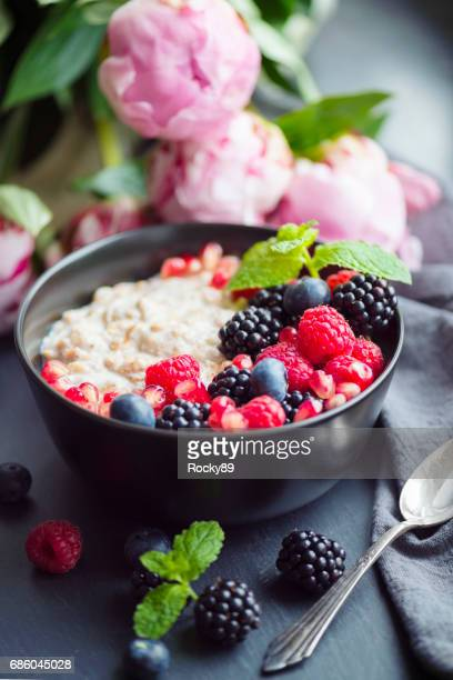 healthy organic porridge topped with berries - oatmeal stock photos and pictures