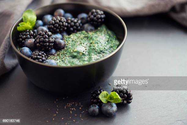healthy organic spirulina porridge topped with berries - antioxidant stock pictures, royalty-free photos & images