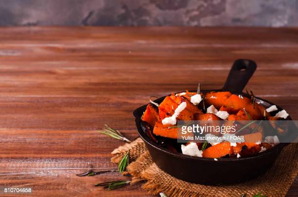 Healthy pumpkin with cheese in pan on table