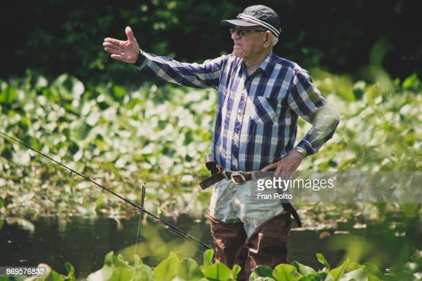 a healthy retired older man out fishing. - baldwin brothers stock pictures, royalty-free photos & images
