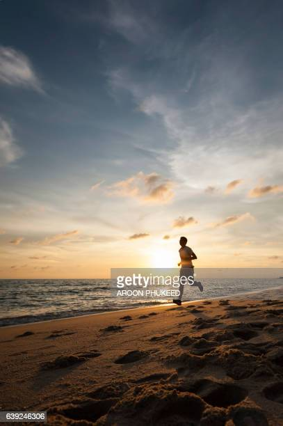 Healthy runner man during sunset on the beach