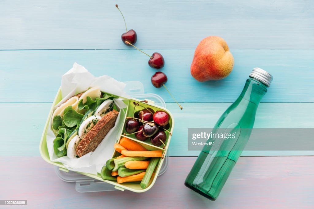 Healthy school food in a lunch box, vegetarian sandwich with cheese, lettuce, cucumber, egg and cress, sliced carrot and celery, cherries and pear : Foto de stock