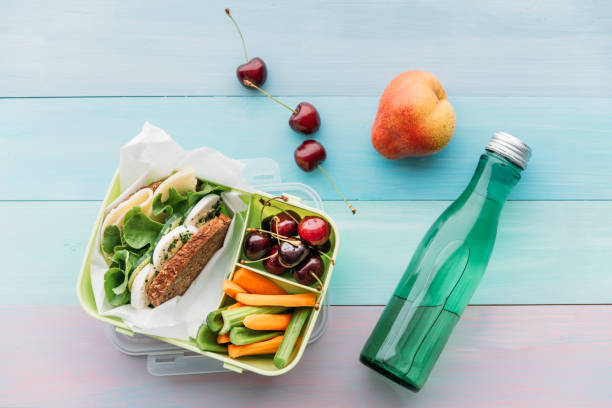 healthy school food in a lunch box, vegetarian sandwich with cheese, lettuce, cucumber, egg and cress, sliced carrot and celery, cherries and pear - preparation stock pictures, royalty-free photos & images