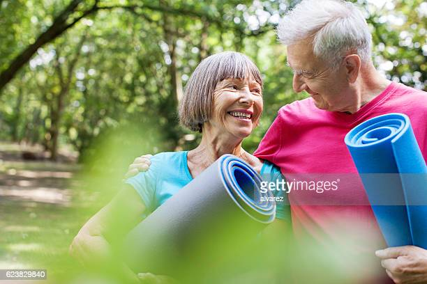 Healthy senior couple with yoga mat in the park