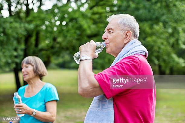 Healthy senior man taking break from exercise in park