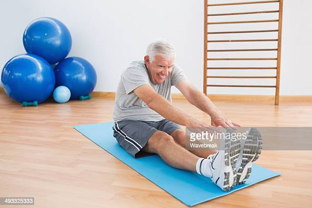 Healthy senior man touching toes