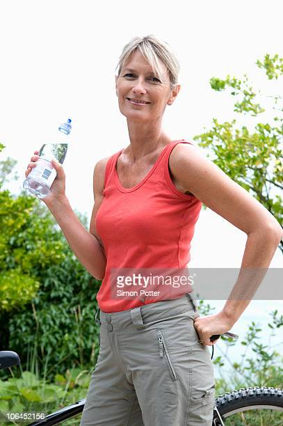 Healthy senior takes drink after workout