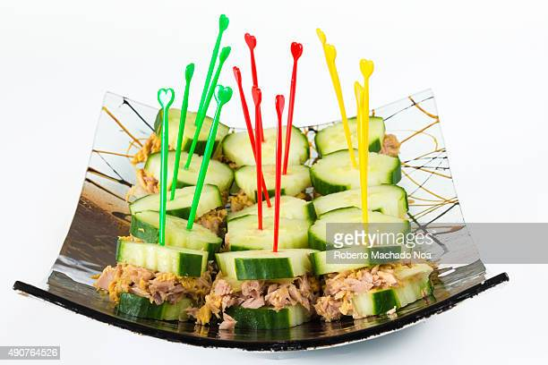 Healthy snack for diabetics tuna and cucumber sandwiches or finger foods made of tuna sandwiched in cucumber slices arranged in a decorative curved...
