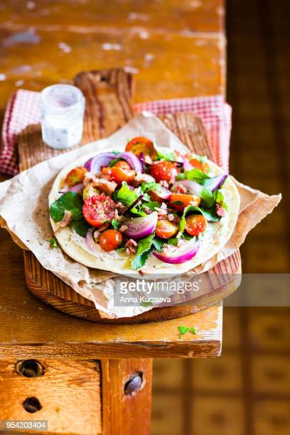 Healthy snack with fresh homemade tortilla, cream cheese sauce, chard leaves, cherry tomatoes, onion served on a wooden cutting board, selective focus. Image with copy space. Picnic food.