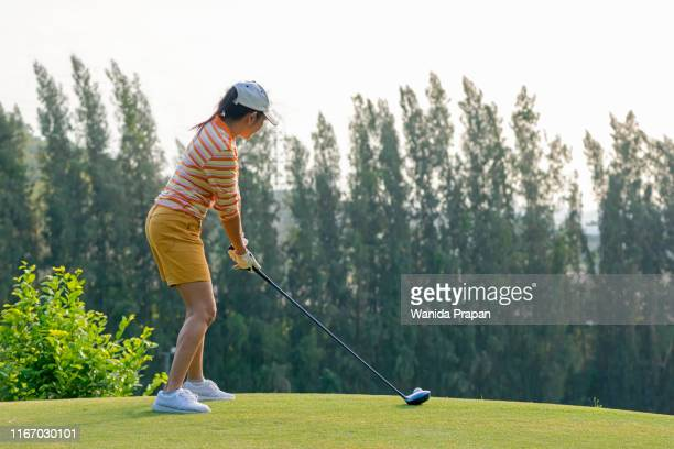 healthy sport. asian sporty woman golfer player doing golf swing tee off on the green evening time, she presumably does exercise. healthy lifestyle concept - ゴルフのスウィング ストックフォトと画像