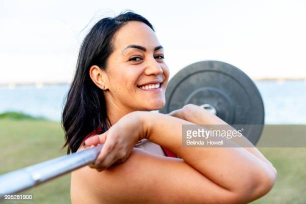 Healthy, strong women by the beach exercising and lifting weights