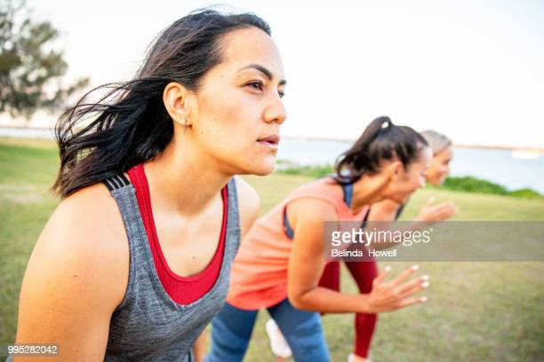healthy, strong women by the beach exercising and lifting weights - thisisaustralia stock pictures, royalty-free photos & images