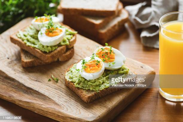healthy toast with avocado, egg, micro greens - avocado toast stockfoto's en -beelden