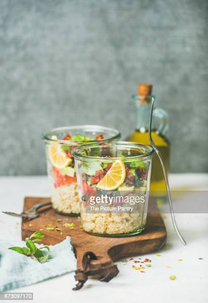 Healthy vegan energy boosting salad with quionoa, avocado, dried tomatoes, basil, olive oil, mint in glass jars, copy space