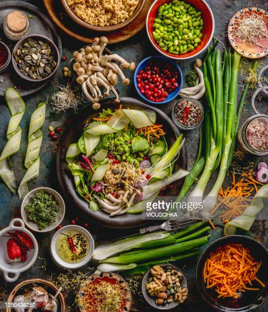 healthy vegan lunch bowl making. detox beautiful buddha bowl with various fresh vegetables, edamame beans, mushrooms, seasoning and pumpkin seeds and nuts topping - salad stock pictures, royalty-free photos & images