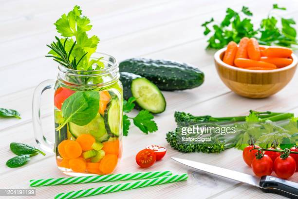 healthy vegetables infused water in a mason jar on white kitchen table. - infused water stock pictures, royalty-free photos & images