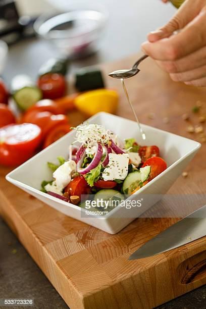Saludable ensalada de verduras, hombre el vertido de aceite de oliva