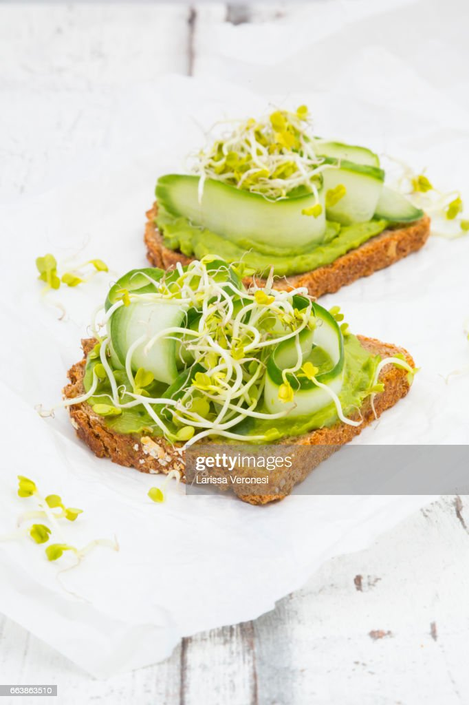 Healthy whole grain bread with avocado, cucumber and sprouts : Stock Photo