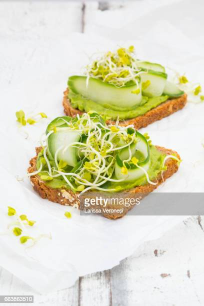 Healthy whole grain bread with avocado, cucumber and sprouts