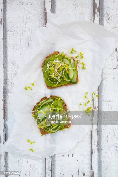 healthy whole grain bread with avocado, cucumber and sprouts - larissa veronesi stock pictures, royalty-free photos & images