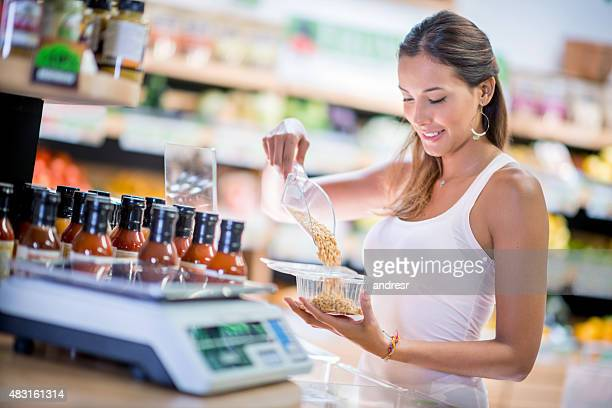 Healthy woman buying cereals at the market