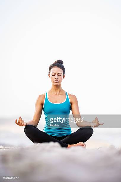 Healthy woman doing meditation on the beach.