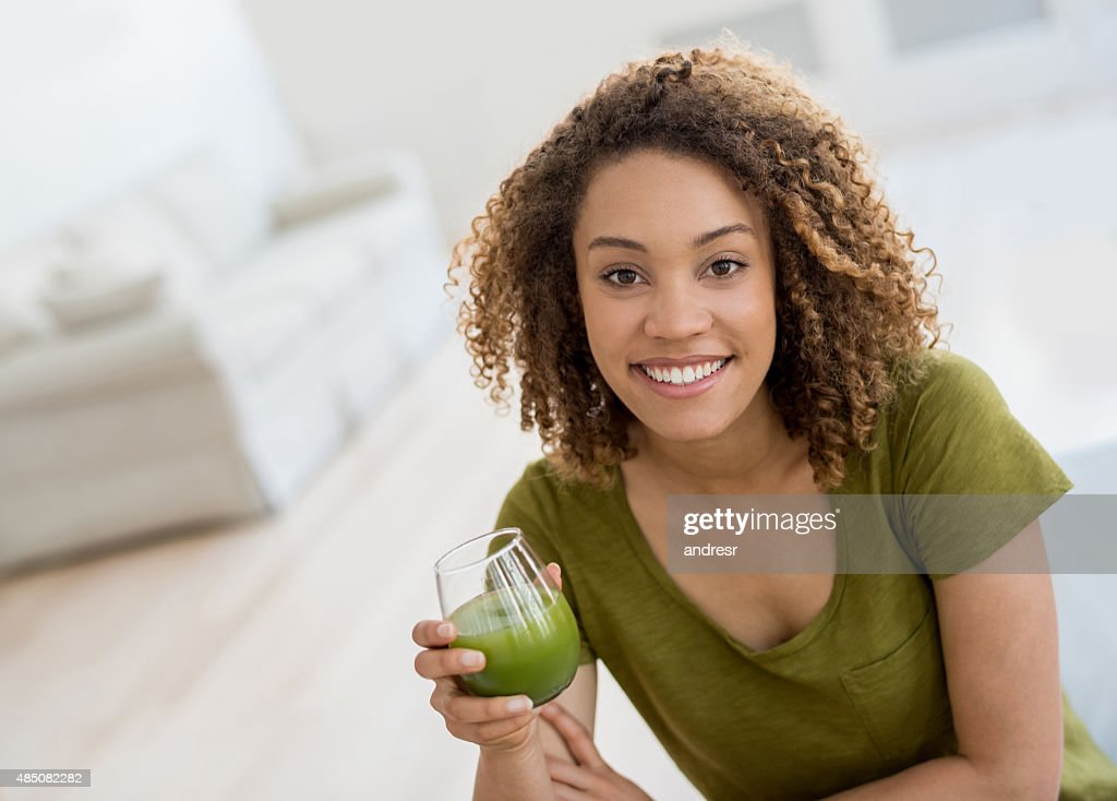 Healthy woman drinking an organic green juice : Stock-Foto