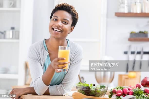 healthy woman drinks orange juice in the morning - lap body area stock photos and pictures