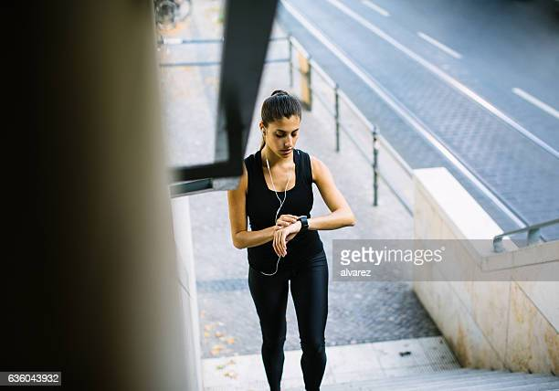 Healthy woman on steps checking smart watch