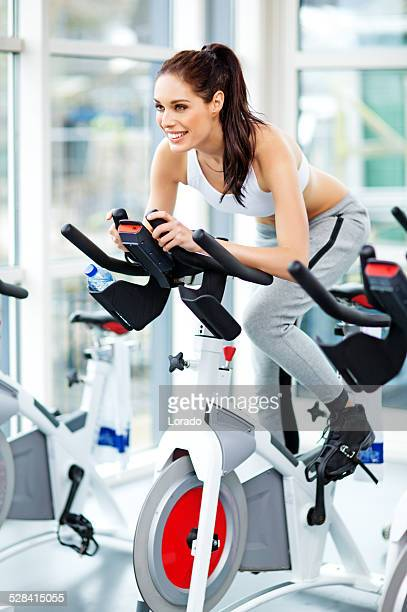 healthy woman riding a bike during spinning training