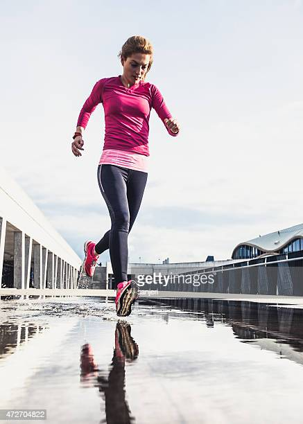 Healthy woman running on wet city street