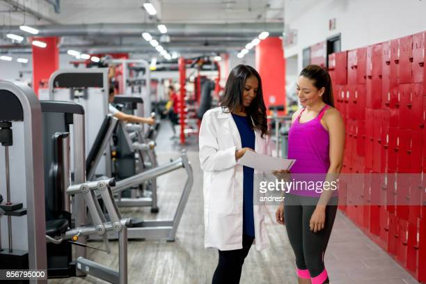 healthy woman talking to the doctor at the gym - sports medicine stock pictures, royalty-free photos & images