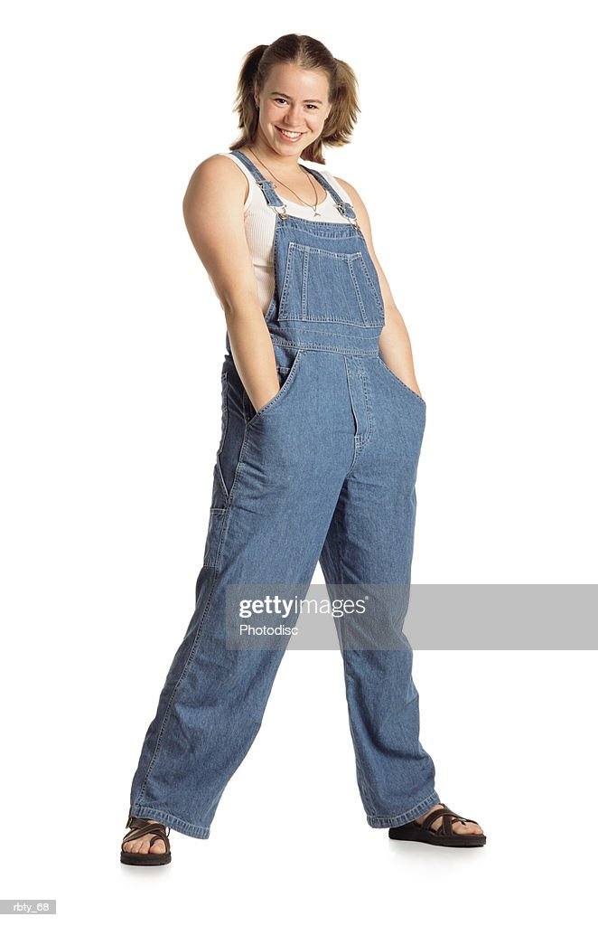 healthy young country girl with pigtails in her short brown hair wearing blue bib overalls over a white tank top with brown sandals and a necklace shoves her hands deep into her pockets with her legs spread apart and smiles at the camera : Stock Photo